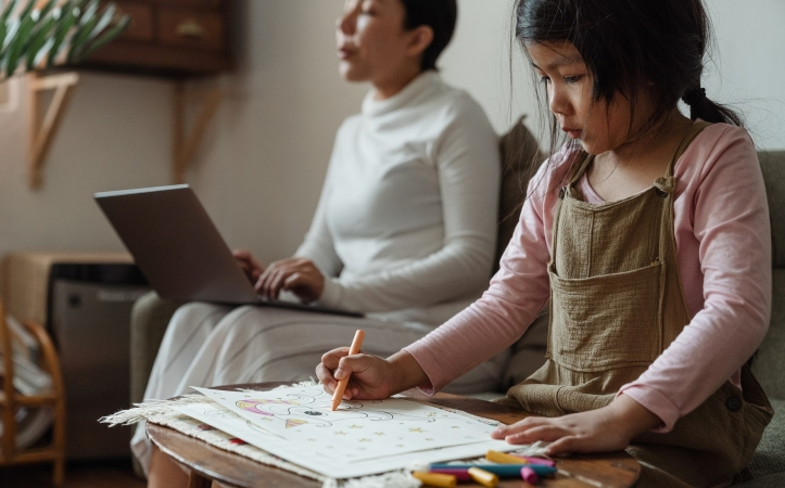 A mother working from home while her young daughter colors nearby.