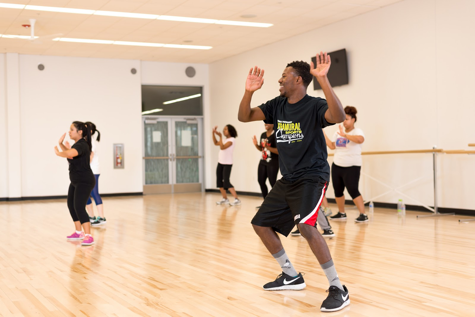 Several students laugh as they enjoy a Zumba class