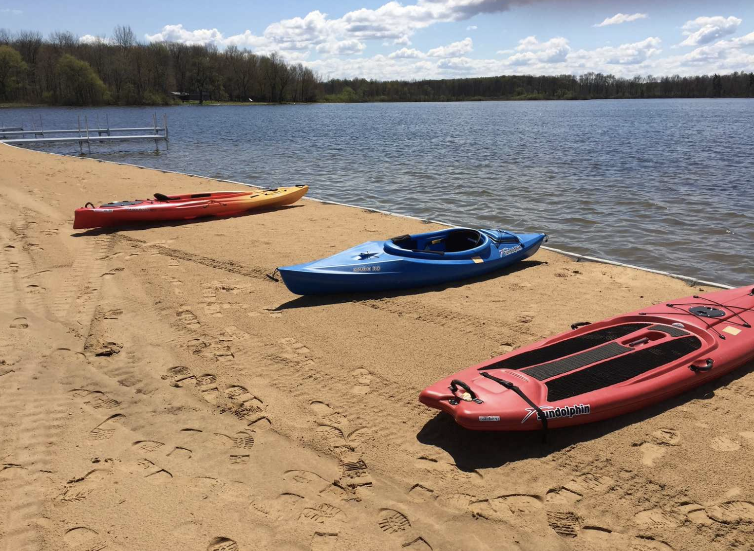 Kayaks and paddle board on the beach next to the water.