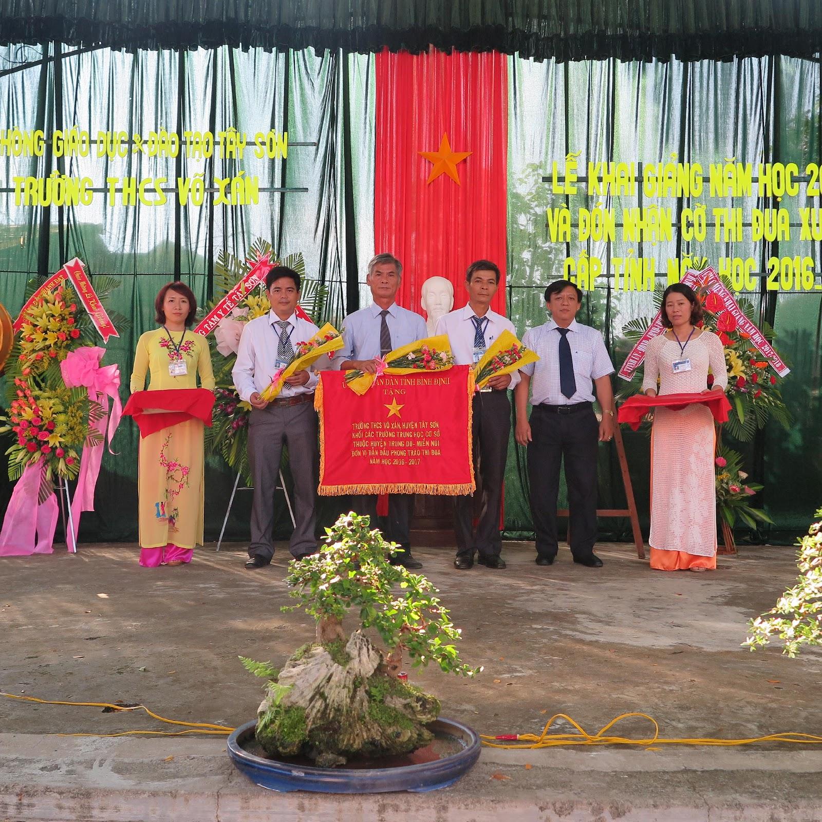 Ông Bùi Văn Mỹ - UVBTV Huyện ủy, Phó Chủ tịch thường trực UBND huyện trao cờ và hoa cho BGH.