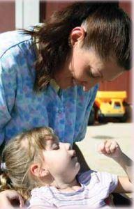 A caregiver looking down at a toddler.