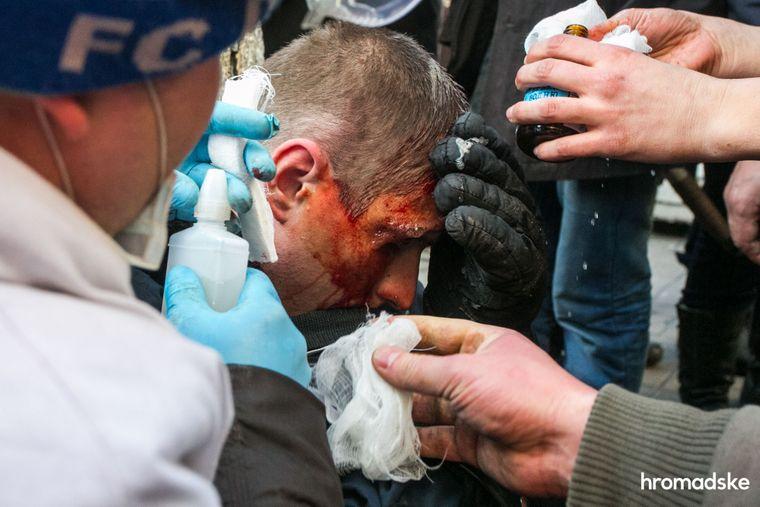 Протестующие оказывают помощь раненому силовику, 18 февраля 2014 года