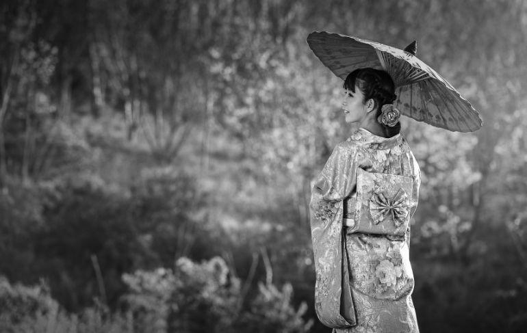 Chinesa com um guarda chuva sorrindo