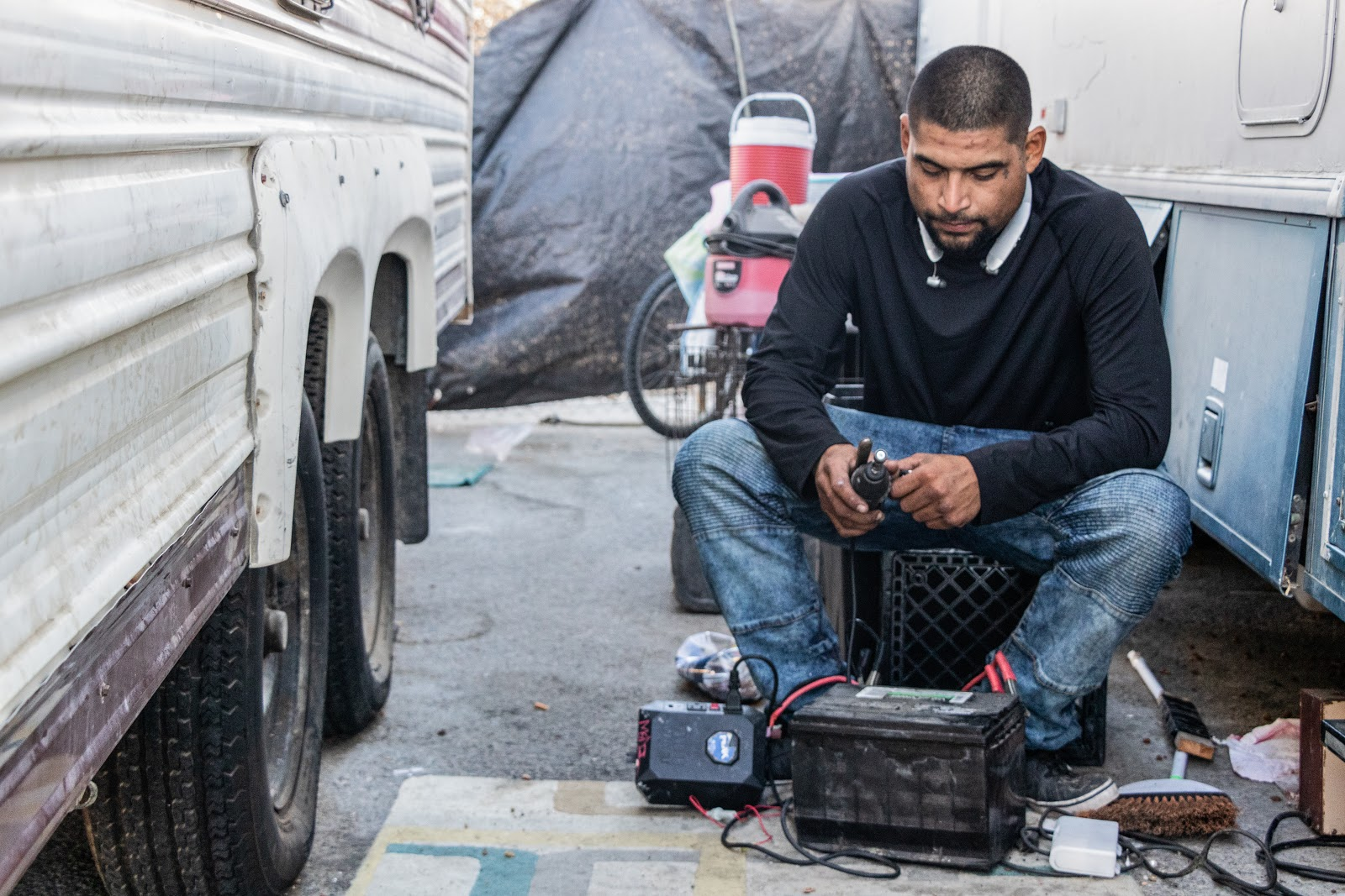 Daniel, an unhoused man who lives in the encampment at North Castro Street, borrows a portable battery from Amanda Jenkins.