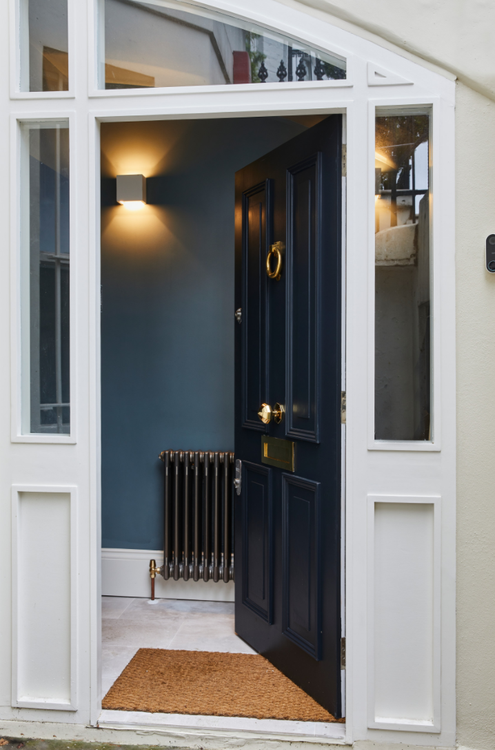Asymmetrical doorway leading to the dark blue hallway in a London home.