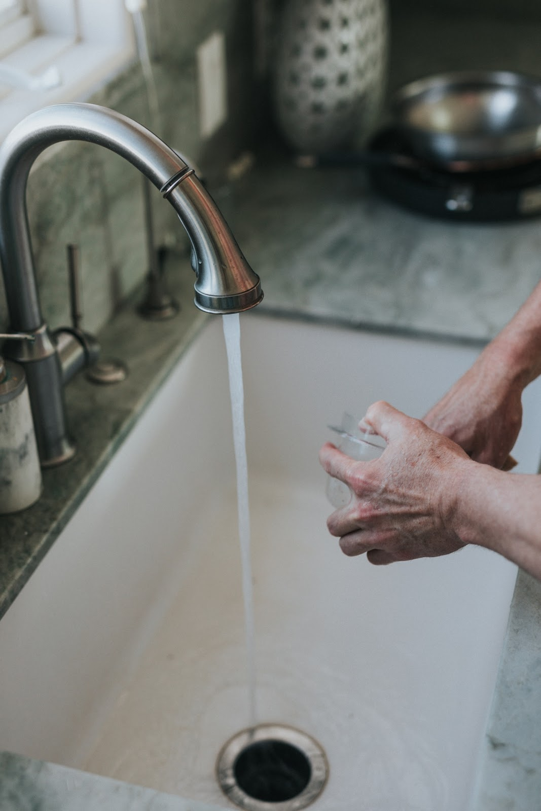 A person cleaning a bowl; doing chores can boost your health