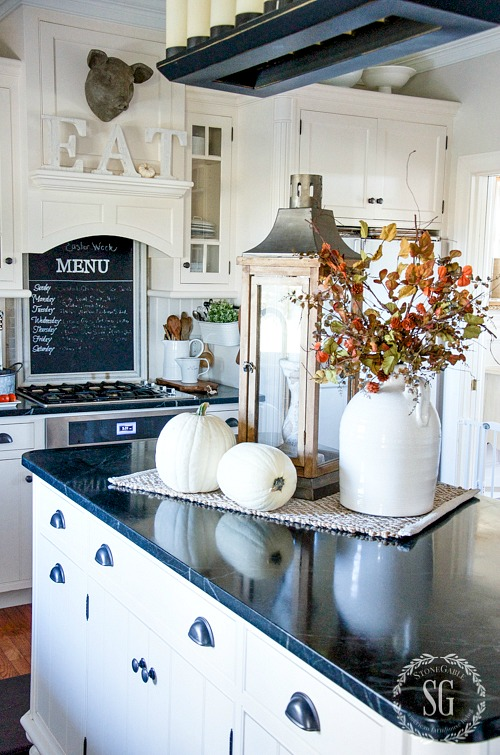 farmhouse kitchen with white shaker cabinets and black countertops. on kitchen island sits two white pumpkins, vase with fall flowers and large rustic lantern