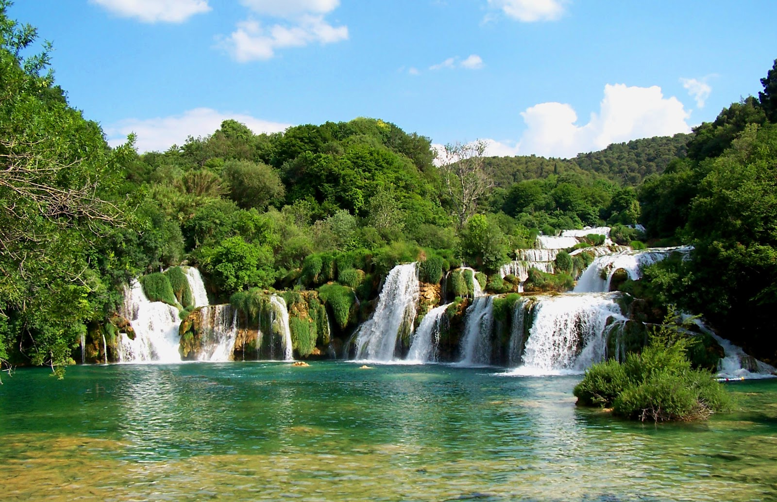 wide waterfall white foamy water going into crystal clear, secluded emerald lake, surrounded by trees. Sunny day in krka national park croatia