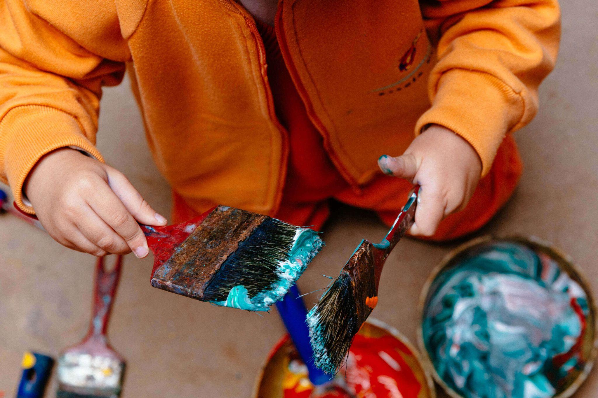 A imagem mostra uma criança manuseando pincéis sujos de tinta.