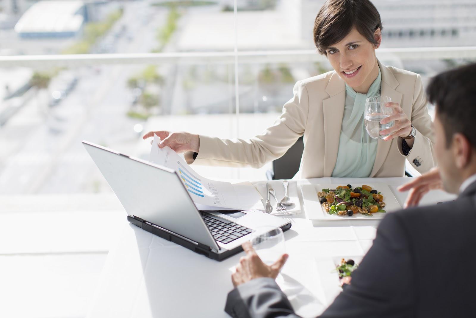 Uma mulher observando o notebook e comendo.