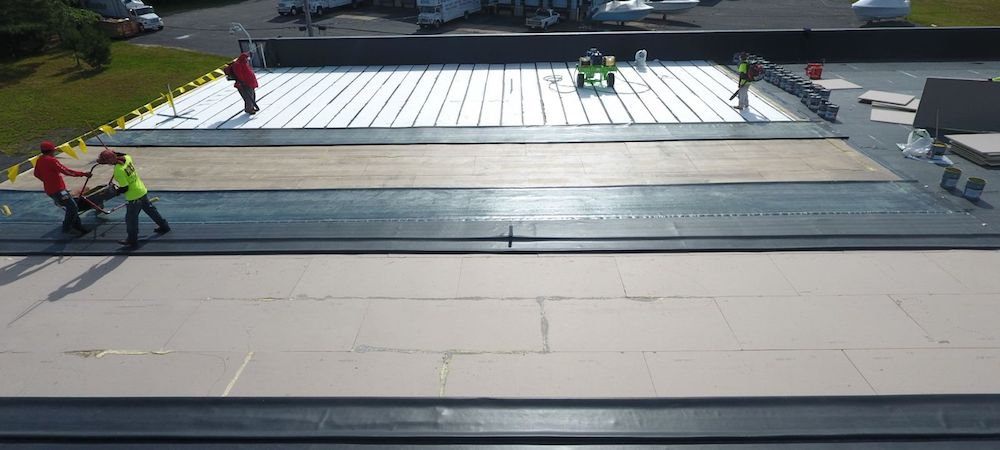Roofers performing a commercial roof repair