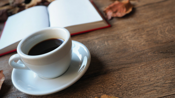 cup of coffee and open book on a table