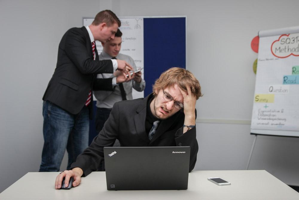 man sitting on chair using gray Toshiba ThinkPad
