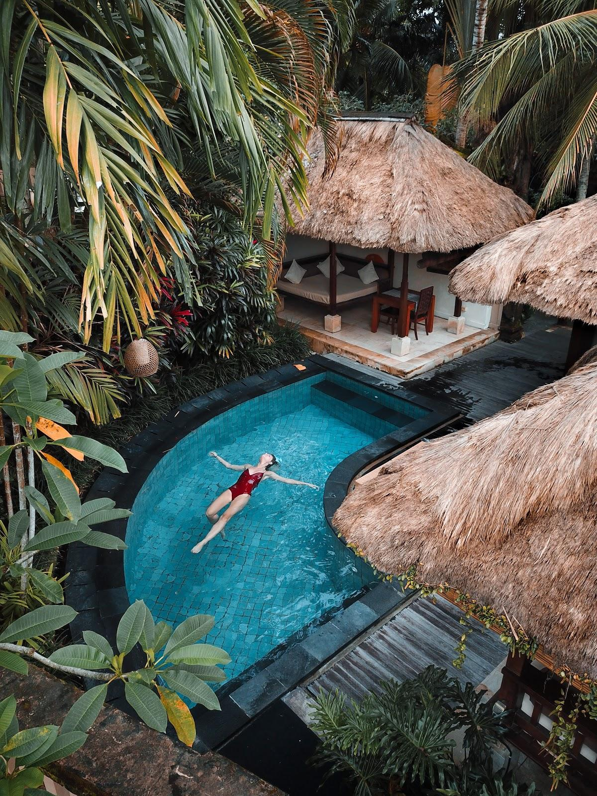 a girl swimming the pool of a tropical hotel