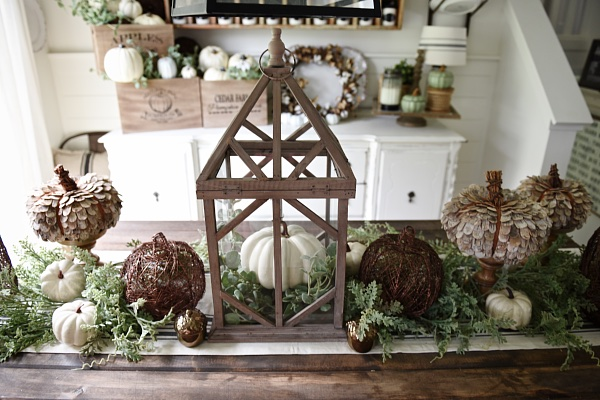 rustic fall themed table centerpiece with a faux wreath and white and brown pumpkins