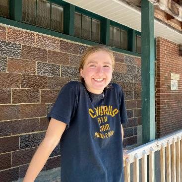 A smiling person in front of a brick wall  Description automatically generated with medium confidence