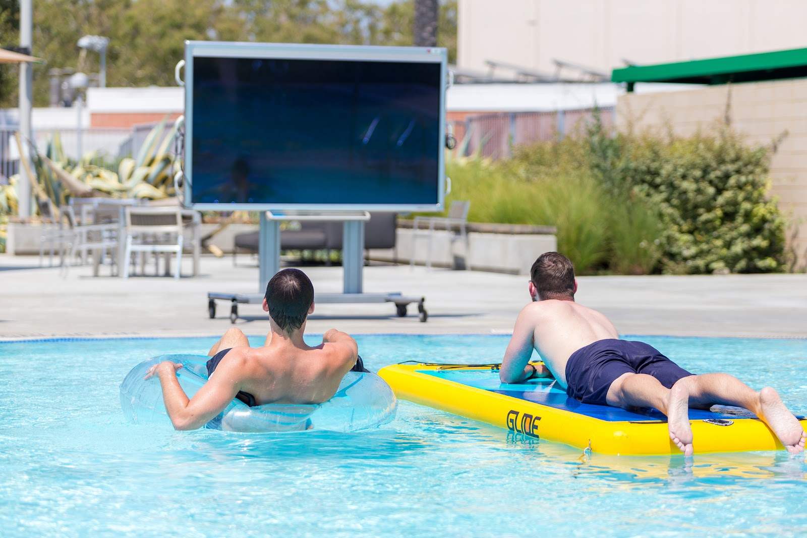 Two guys on floats watching a movie