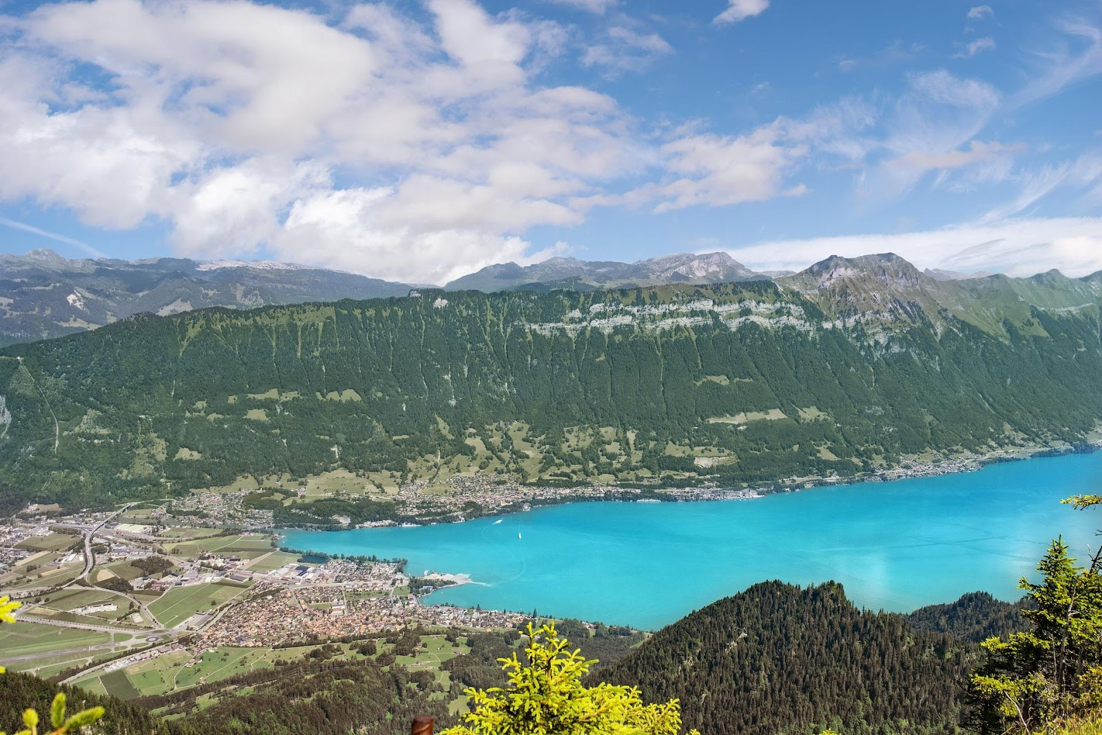 interlaken in the summer seen from above the alps mountains town and blue lake switzerland