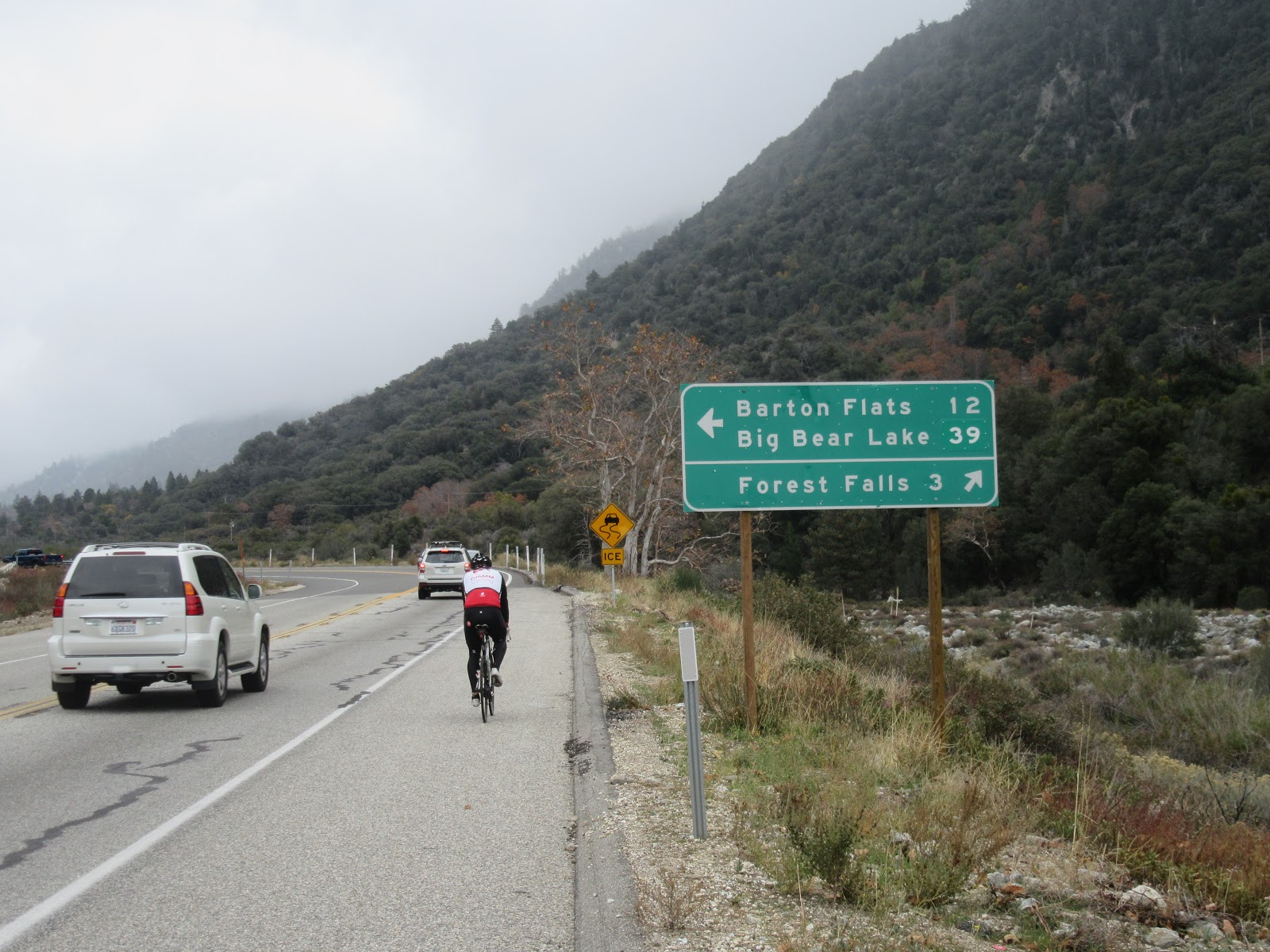 Cycling up Hwy 38 to Onyx Summit  - cyclist and road sign to Valley Falls