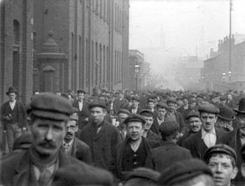 Crowd of English working men outside of a factory, with a boy of about 12 years among them.