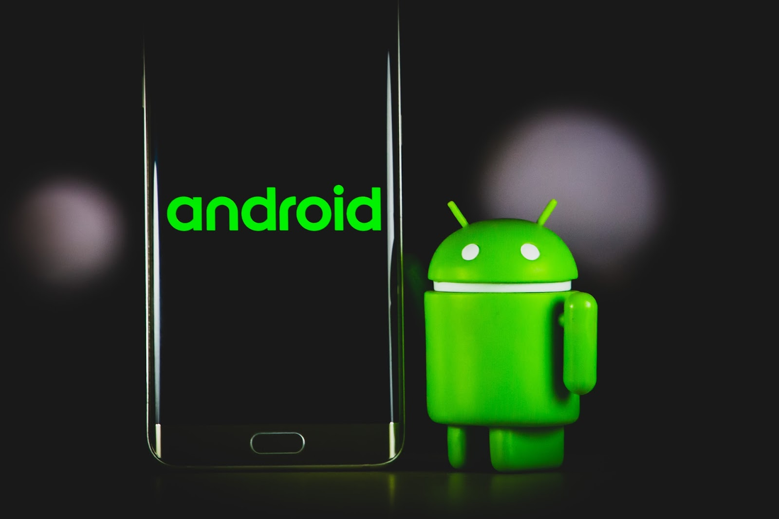 "A phone with green ""android"" text stands up next to a figurine of the android mascot, Bugdroid."