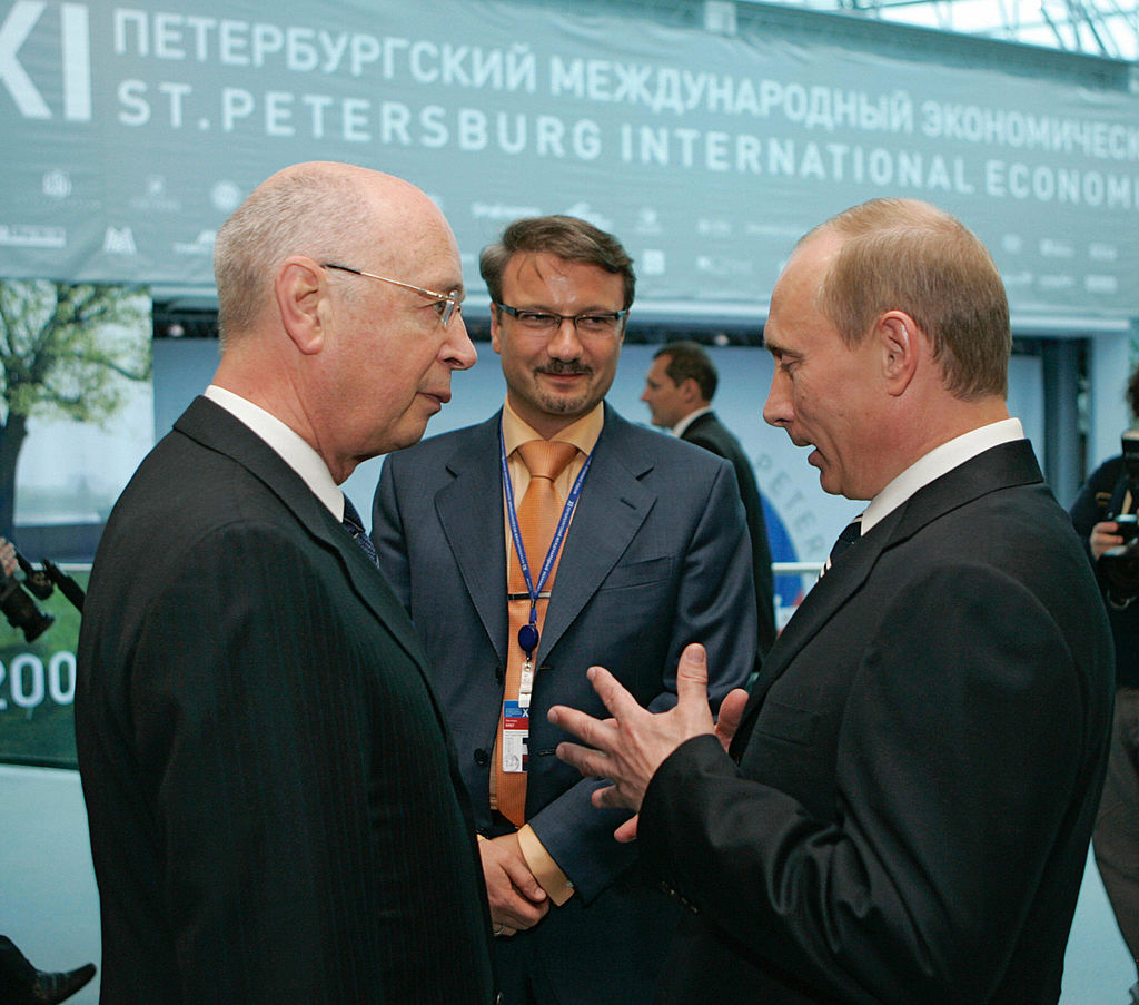 President of the World Economic Forum in Davos Klaus Schwab (L) speaks with Russian President Vladimir Putin (R) as at-the-time Russian Economic Development and Trade Minister German Gref (background) looks on in St. Petersburg on June 9, 2007. The choice of partnering with Russia's largest bank to simulate a digital pandemic crisis is curious considering the mainstream media's anti-Russia narrative.
