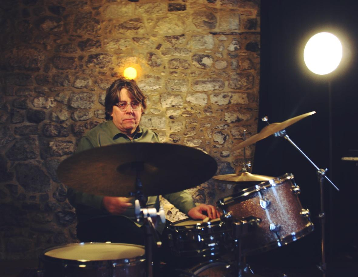 A person playing a drum set  Description automatically generated with low confidence