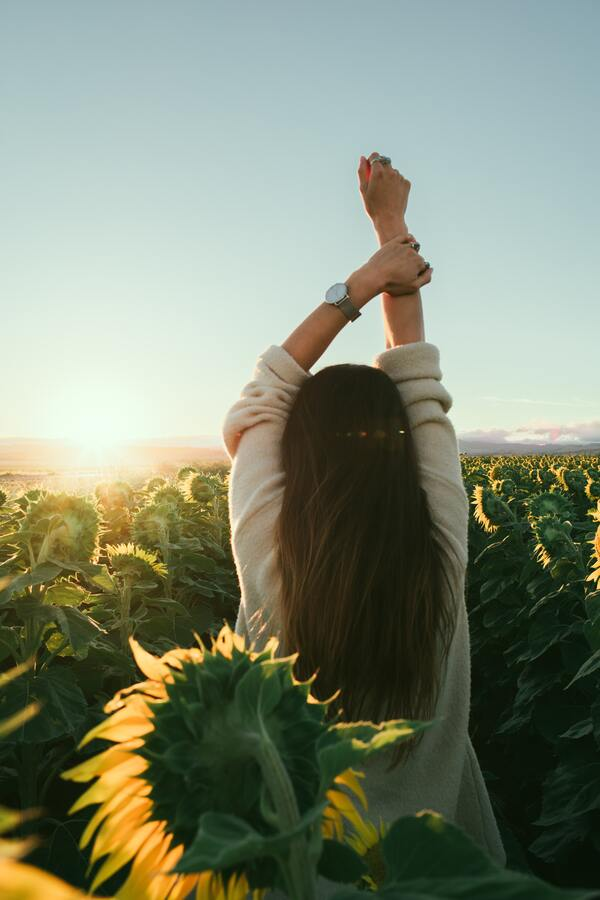 Foto de uma mulher em um campo de girassóis, de costas, com as mãos para cima.