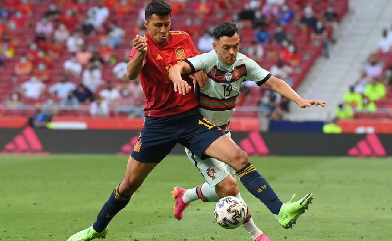 Alt: Spain's Rodri does battle for the ball with Pote of Portugal - Photo by David Ramos/Getty Images