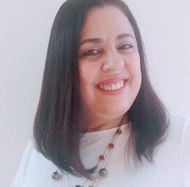 A imagem mostra Rosana sorrindo. Ela veste uma blusa branca sem decote, usa o mesmo colar da outra foto, de bolinhas cinza e âmbar. O cabelo dela vai até o ombro e é liso.
