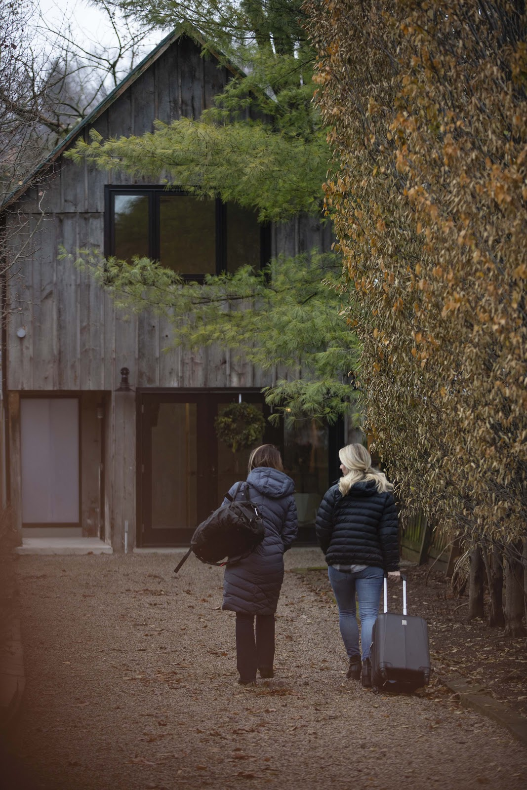 two women with suitcases going towards a wooden house
