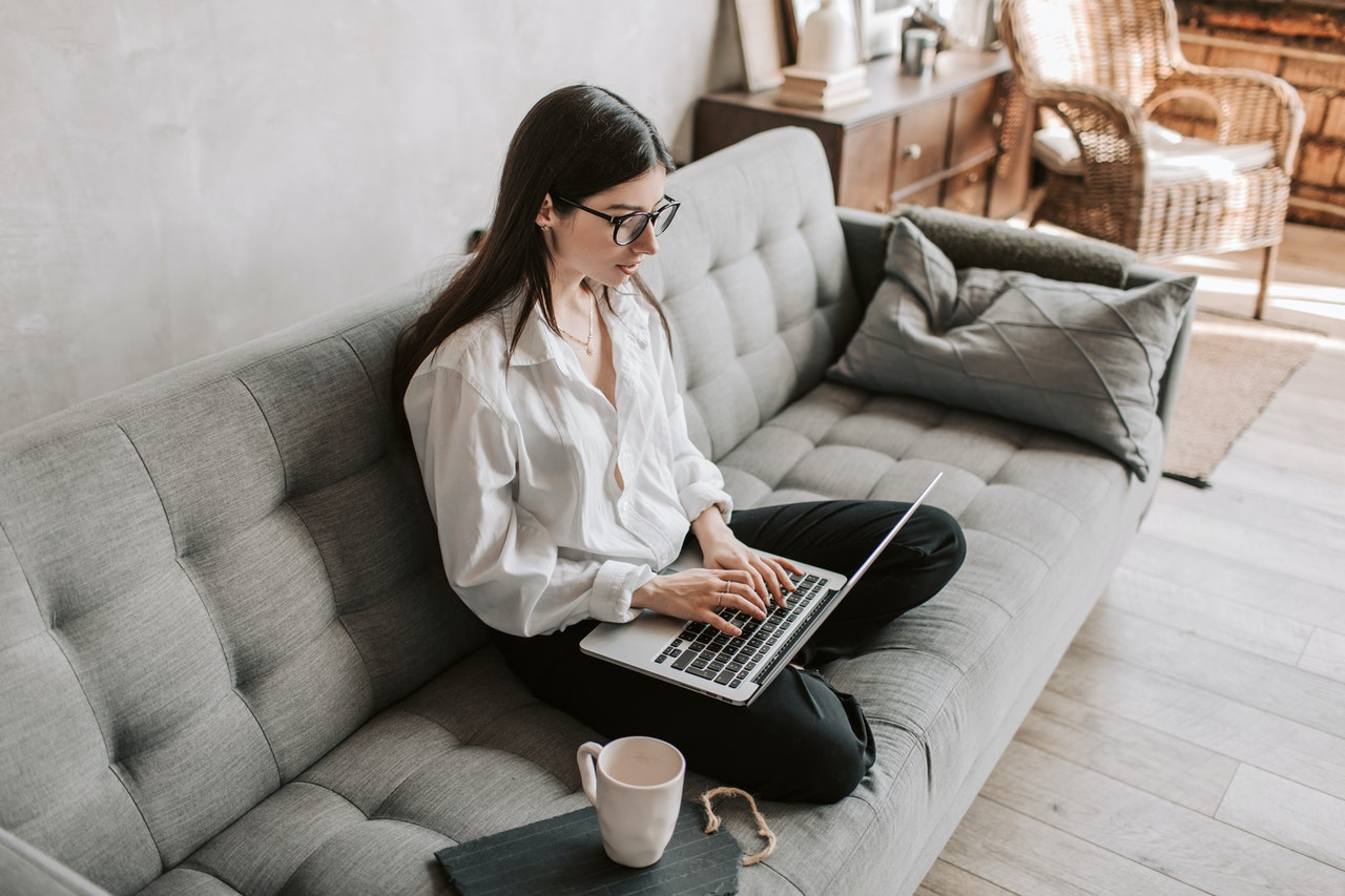 woman sitting cross-legged on a couch and working on a laptop.