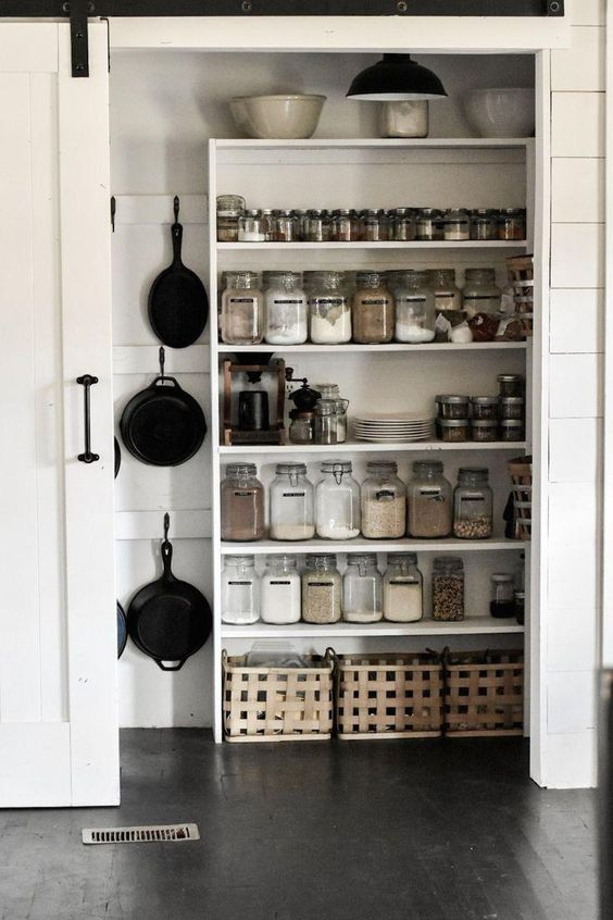 white farmhouse pantry with hanging pans, glass jars, black and white sliding farmhouse door