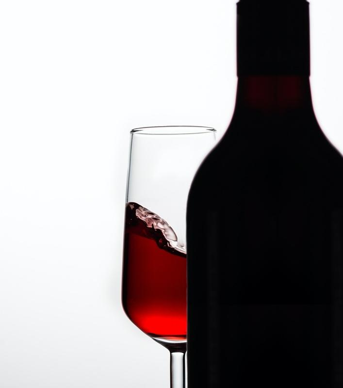 A bottle and a glass of red wine  Description automatically generated