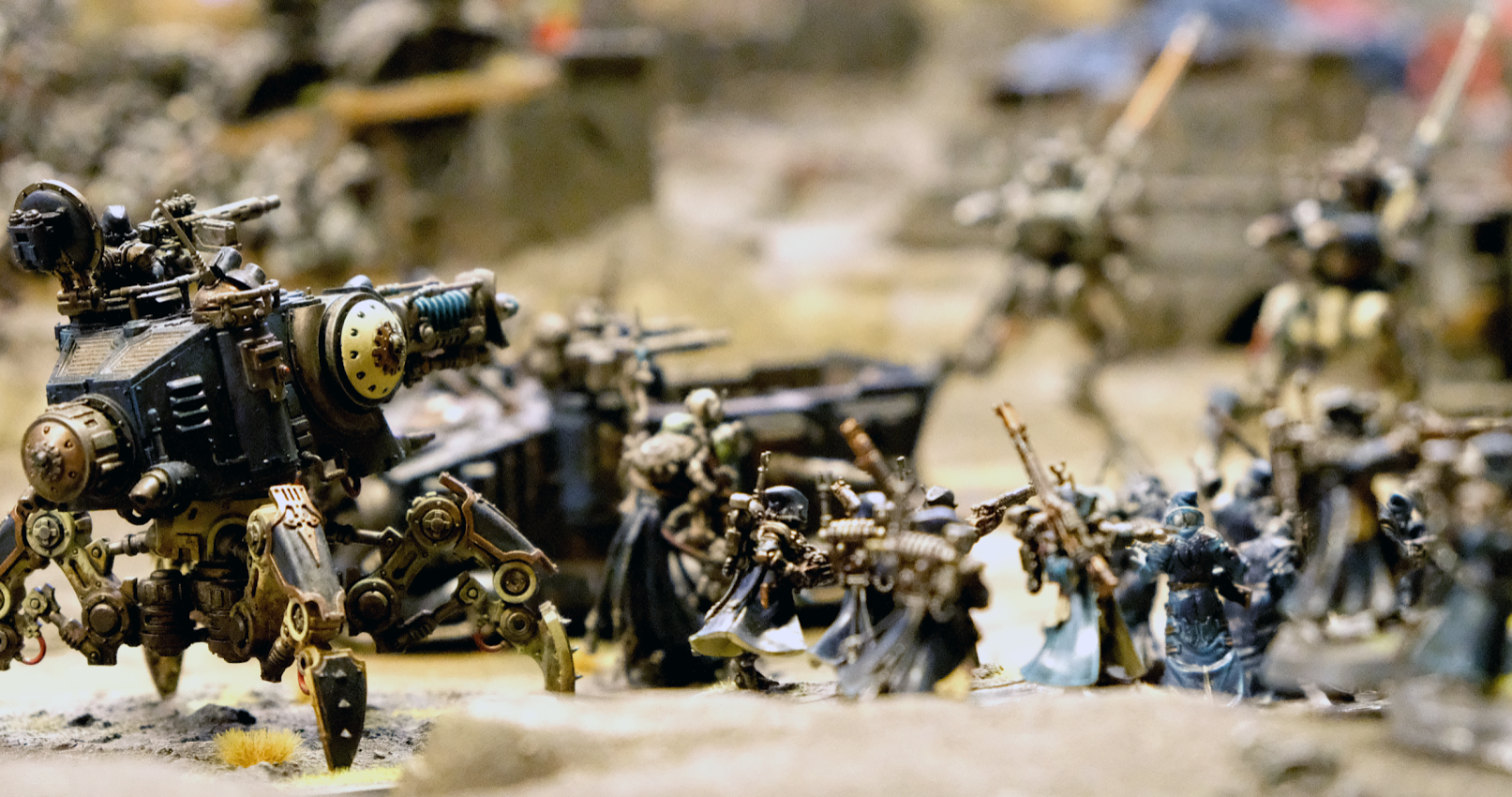 A large game of Warhammer in progress with a blue spider tank in focus at the rear of a troop charge