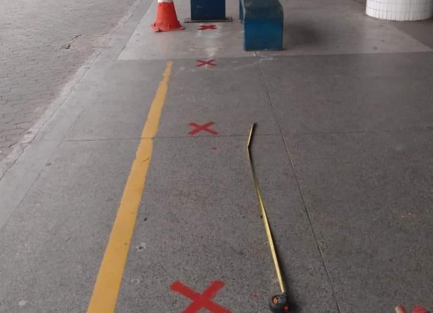 A imagem mostra dois 'X' no chão feitos com fita e uma trena medindo a distância entre eles