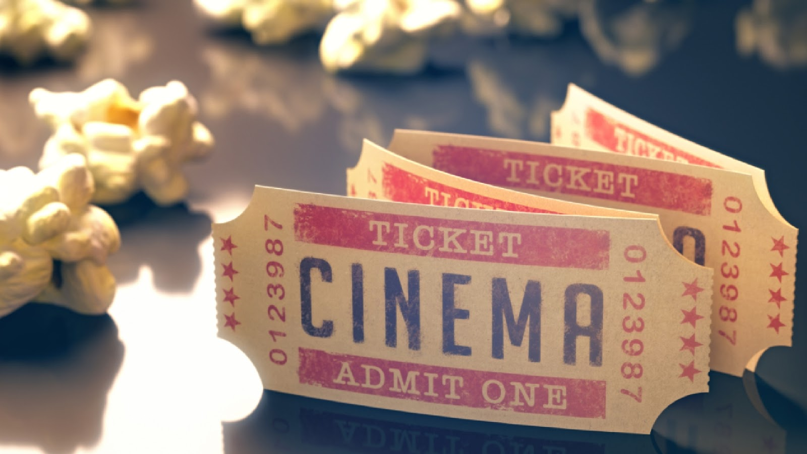 A couple of cinema tickets in front of scattered popcorn.