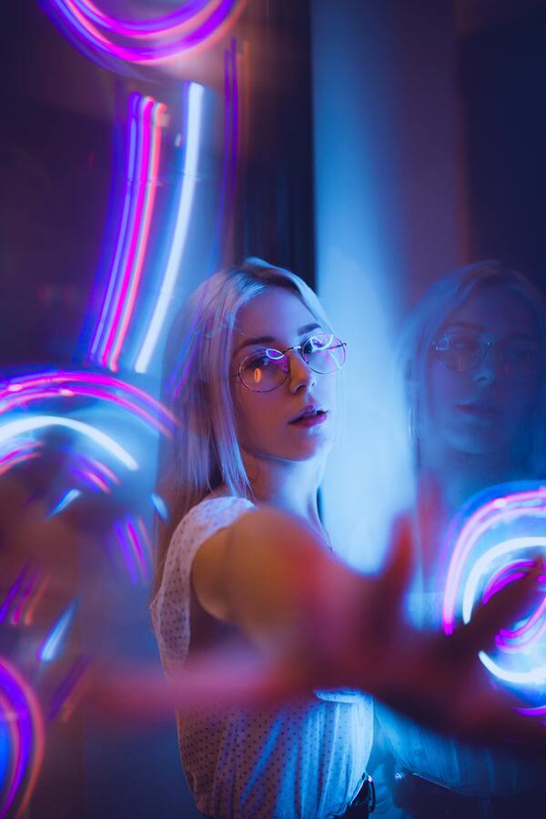 Fotos de uma mulher estendendo a mão com edições de luzes e neon em volta dela