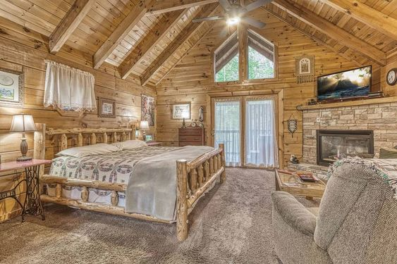 cabin bedroom with log style bed and stone fireplace