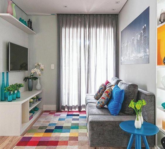 Sala e sofá cinzas, com acessórios coloridos como tapete, mesa de centro, almofadas e enfeites.