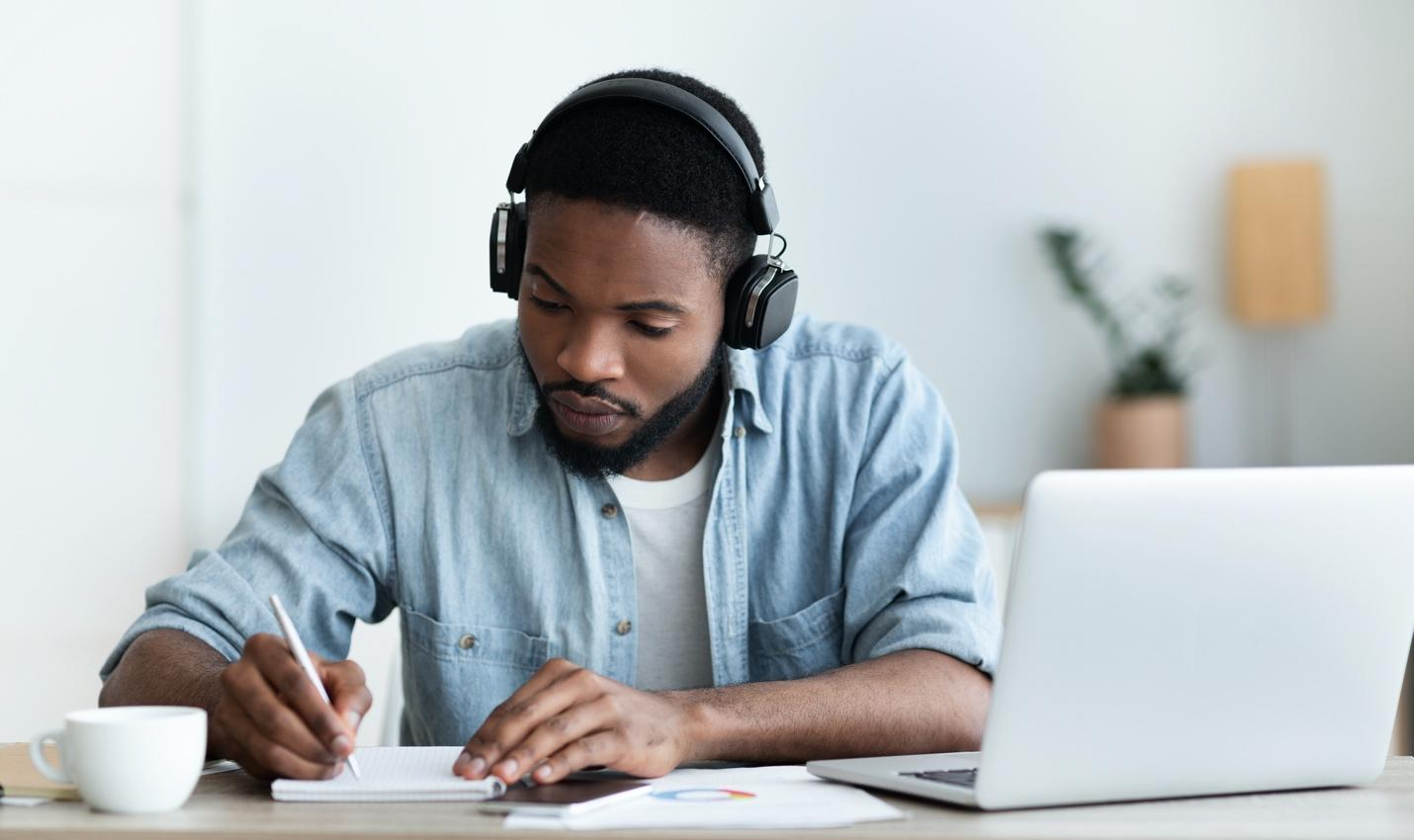 African American man wearing headphones and studying in front of a computer