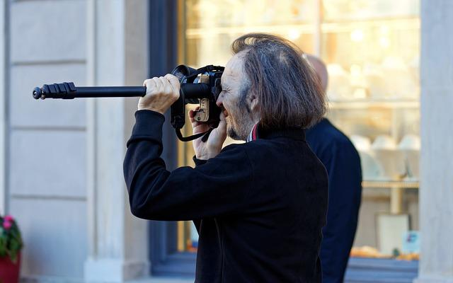 man holding camera up to his face with a monopod
