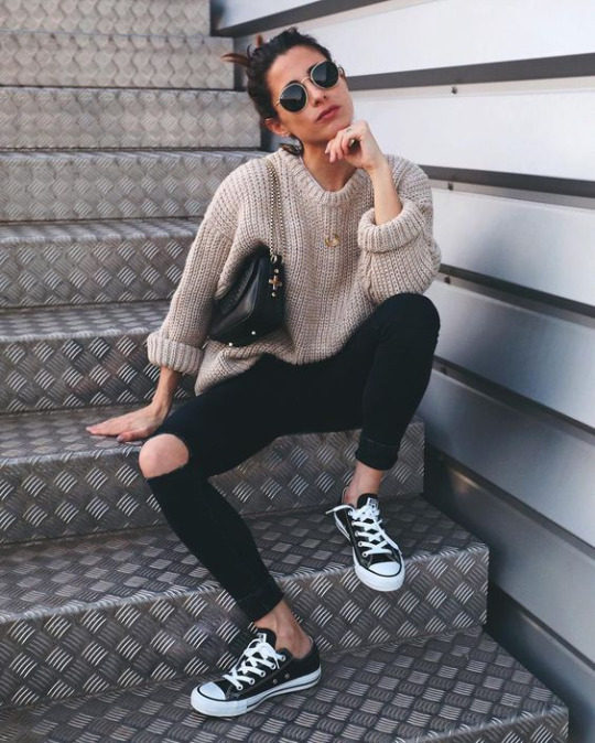 woman in torn pants and bulky sweater