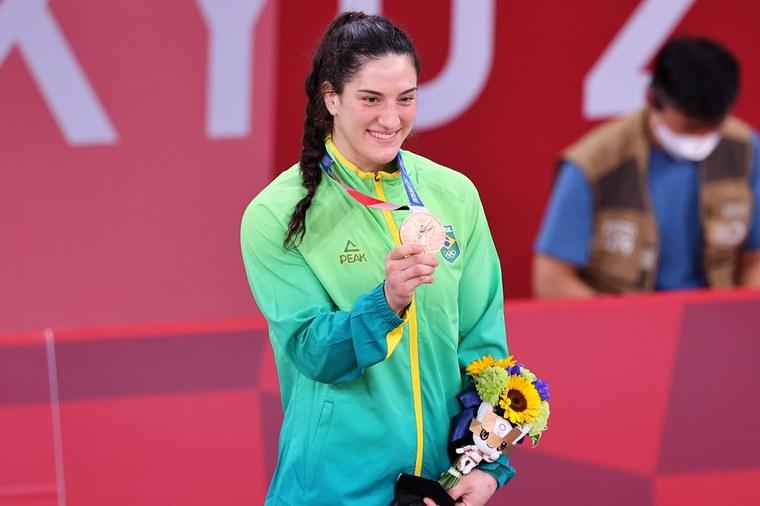 Imagem da atleta Maya Aguiar em pé de cabelos escuros presos em uma trança, veste roupa azul, verde e amarela, segura medalha de bronze em uma mão e flores em outra. Foto: Rede do Esporte.