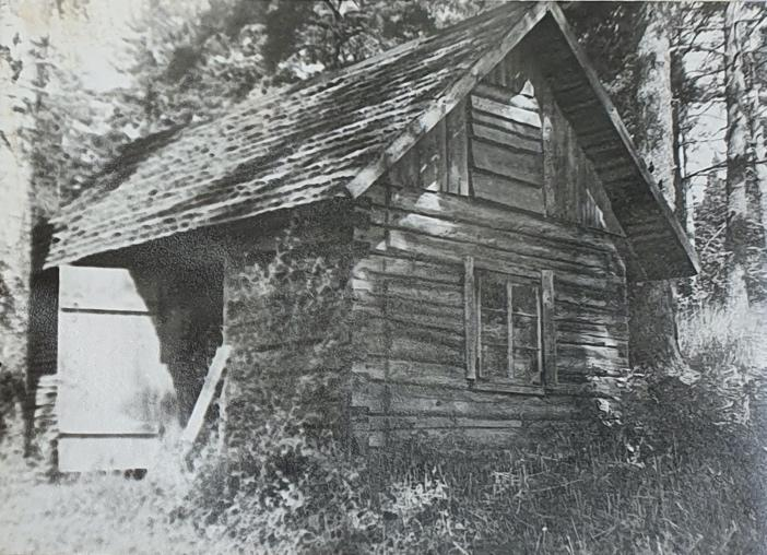 An old barn in front of a houseDescription automatically generated