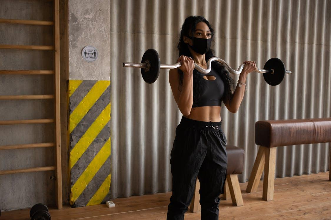 Black sportswoman in face mask exercising with barbell in gymnasium