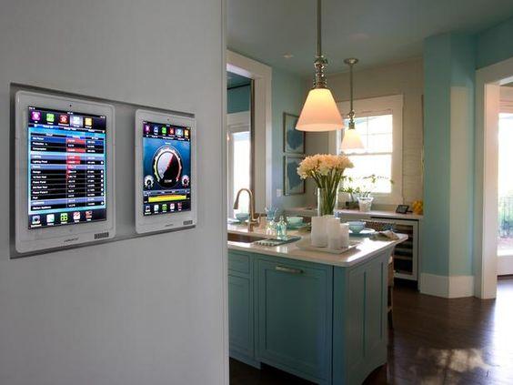 Imagem de duas telas touch instaladas em uma das paredes de uma casa inteligente.