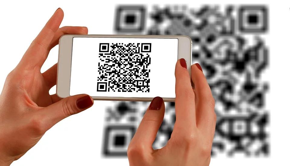 imagem de uma mulher segurando um celular com QR code