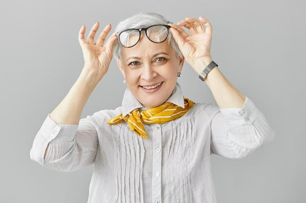 Beautiful fashionable caucasian woman pensioner with farsightedness taking off her eyeglasses to focus on closer objects, smiling broadly . mature people, aging and vision problem concept Free Photo
