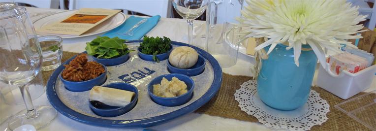 A festive Seder Plate with the six traditional items: Maror (bitter herbs), Charoset (apple mixture), Karpas (vegetable), Zeroa (roasted lamb shank bone), Beitzah (roasted egg).
